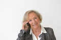 Blond senior woman having a conversation on mobile with friendly facial expression phone portrait with copy space gray Royalty Free Stock Photo