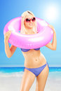 Blond sexy female in bikini holding a pink swimming ring and enj enjoying on sunny day on beach Stock Photography