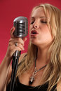 Blond singing into retro microphone Stock Photography