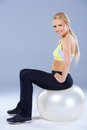 Blond sporty woman sitting on fitness ball over gray background Stock Photography
