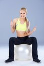 Blond sporty woman sitting on fitness ball over gray background Stock Photos