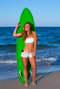 Blond surfer teen girl holding surfboard on beach blue Royalty Free Stock Photos