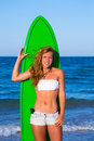 Blond surfer teen girl holding surfboard on beach blue Royalty Free Stock Images