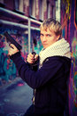 Blond teenager holding a pistol and knife at the graffiti wall in the lane Royalty Free Stock Images