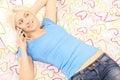 Blond wijfje die in bed liggen en op een telefoon spreken Royalty-vrije Stock Foto's