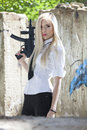 Blond woman with automatic gun young holding a handgun dressed in white blouse and tie outdoor Stock Images