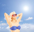 Blond woman in bikini relaxing against a blue sky shot with tilt and shift lens Stock Image