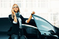 Blond woman calling on the phone business leaning car door Stock Photography