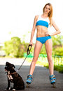 Blond woman with dog on roller skates in the park Stock Photography