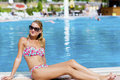 Blond  woman enjoying the summer vacation laying on sunbed in a tropical garden Royalty Free Stock Photo