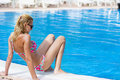 Blond woman enjoying the summer vacation laying on sunbed in a tropical garden pretty sitting pool Royalty Free Stock Photo