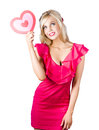 Blond woman with heart sign a beautiful in a red dress a red Stock Image