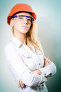 Blond woman with a helmet and glasses serious business young on her head looking at camera blue background Royalty Free Stock Photos