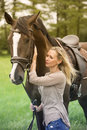 Blond woman and her horse in nature Royalty Free Stock Photo