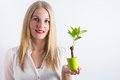 Blond woman holding a small green tree Royalty Free Stock Photos
