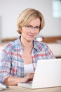 Blond woman at home with laptop Royalty Free Stock Image