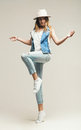 Blond woman jumping in hat and denim waistcoat jeans Royalty Free Stock Photos