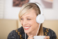 Blond woman listening music and drinking coffee beautiful smiling while to on large white headphones drink a cup of Royalty Free Stock Photography