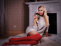 Blond woman near fireplace with champagne glass Royalty Free Stock Photo