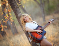 Blond woman playing an acoustic guitar a beautiful in forest with autumn colors Stock Photo
