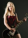 Blond woman playing electric guitar photo of a sexy female a black wearing a red corset Stock Photo