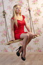 Blond woman in a red dress sitting on a swing against a backdrop of wallpaper with roses Royalty Free Stock Photo