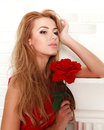 Blond woman with red rose in studio, girl and flower Royalty Free Stock Photo