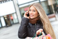 Blond woman shopping and phoning Royalty Free Stock Photos