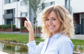Blond woman showing her new apartment outside in front of the building Royalty Free Stock Photography