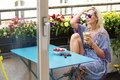 Blond woman sitting on balcony with coffee and cherries a glass of a bowl of Stock Photography