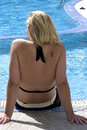Blond woman sitting by swimming pool Stock Photo