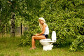 Blond woman sitting on a toilet bowl and reading a book Royalty Free Stock Photo