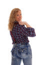 Blond woman standing from the back a portrait image of a middle age in jeans and a checkered shirt looking over her shoulder Royalty Free Stock Photo