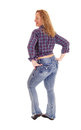 Blond woman standing from the back a portrait image of a middle age in jeans and a checkered shirt looking over her shoulder Stock Image