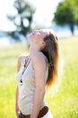 Blond woman standing in meadow enjoying sun Royalty Free Stock Photo