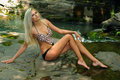 Blond woman in swimsuit sitting at oasis pool in mountains Royalty Free Stock Photo