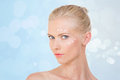 Blond woman testing salve on her face nordic girl with cream front and cheekbone blue background Stock Photography
