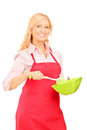 Blond woman wearing red apron and holding kitchen utensil isolated on white background Royalty Free Stock Photography