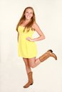 Blond in yellow dress and cowboy boots Royalty Free Stock Photo