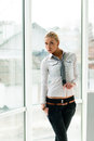 Blond young beautiful business woman standing relaxed near window at her office Royalty Free Stock Photo