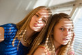2 blond young women beautiful sisters or girl friends in blue dress having fun posing looking at camera against sun lighted rays Royalty Free Stock Photo