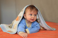 The blonde baby covered by a blanket charming with blue eyes joyfully smiles Stock Photo
