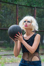 Blonde in basketball the girl the image of frivolous with bright makeup plays a ball Royalty Free Stock Photography