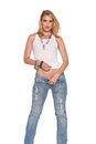 Blonde beautiful slender woman in a white top and jeans Stock Photos