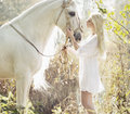 Blonde beautiful woman touching mejestic horse Royalty Free Stock Photo