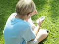 Blonde boy sitting on grass listening to mp player rear view elevated view Stock Images