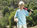 Blonde boy standing in park with softball bat and ball smiling front view portrait Royalty Free Stock Images
