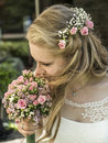 Blonde bride inhale smell aroma of a flower bouquet from roses holding during wedding marriage Royalty Free Stock Photo