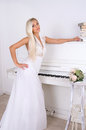 Blonde bride near the piano Royalty Free Stock Photo