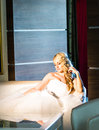 Blonde bride sitting on the armchair in room Royalty Free Stock Photo